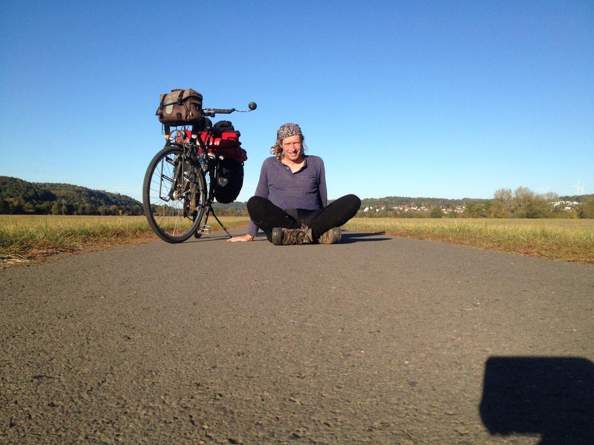 Underfoot-Aufnahme vom Fahrradhelm aus, der als Stativ diente und auf dem Radweg lag. Ein Mann mit Radlerkleidung im Schneidersitz rechts neben seinem Fahrrad. Viel Teer im Vordergrund und blauer Himmel, dazwischen ein schmaler Streifen Grün als Horizont.linie