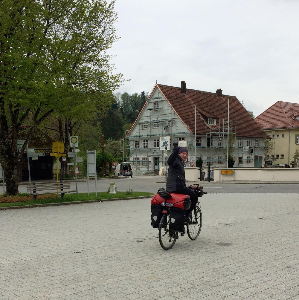 Irgendlink winkt vom fahrenden Radel aus zurückblickend vorwärts.