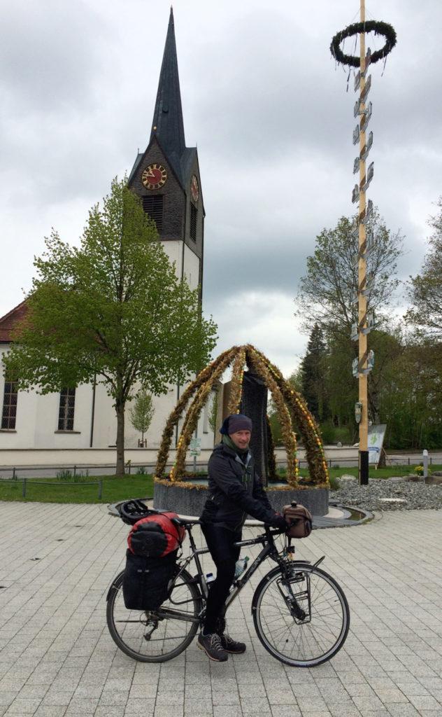 Herr Irgendlink samt vollgepacktem Rad auf dem Gestratzer Dorfplatz vor Pflanzenskultpur, Maibaum und alter Kirche.