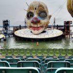 Bühnenbild der Seebühne in Bregenz mit einem rieigen Gruselclownkopf hinter leeren Stuhlreihen.