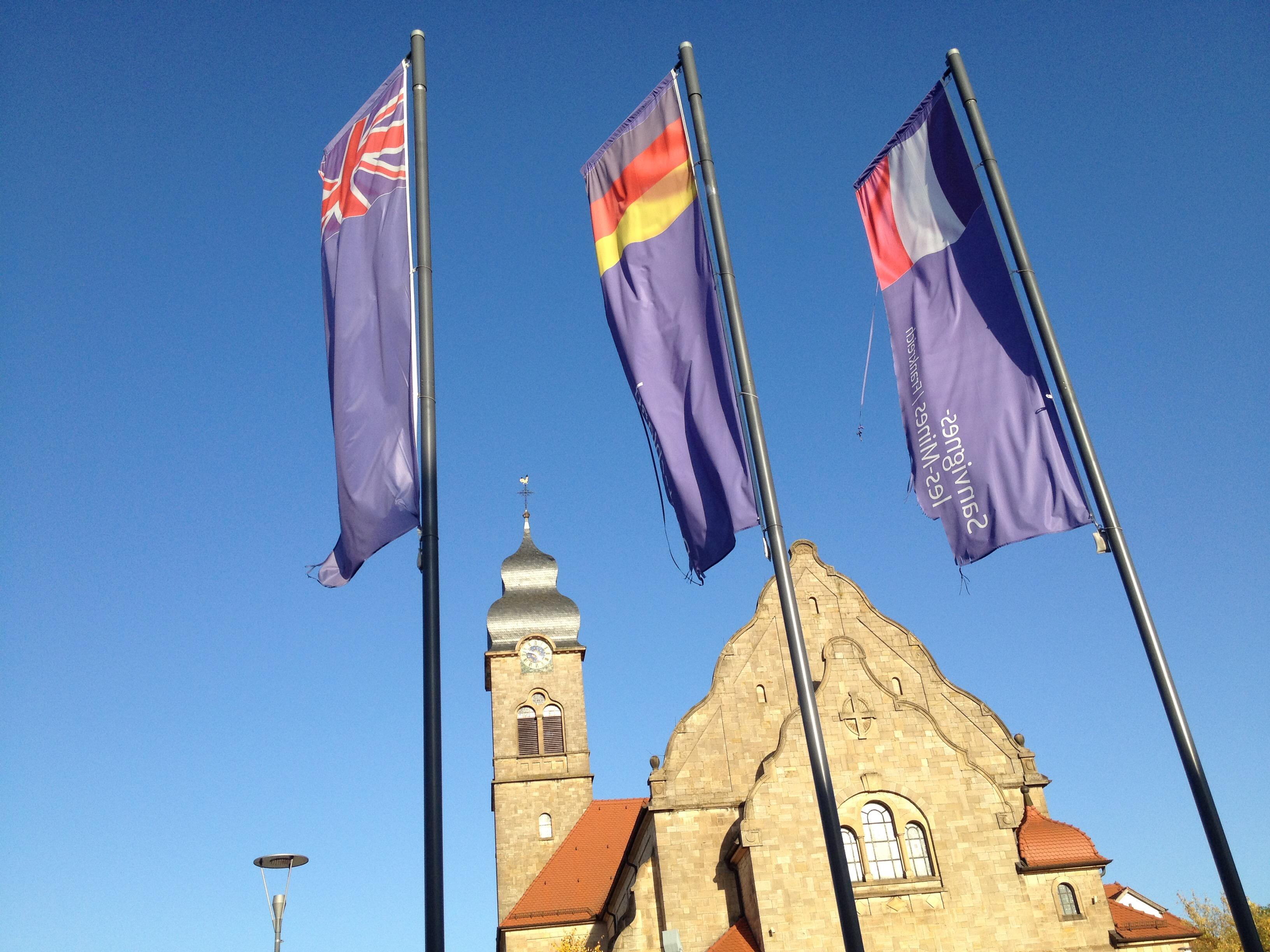 Schräge Aufnahme dreie Europafahnen vor Sandsteingelber barocker Kirche.