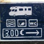 Ein handgemaltes Campingplatz-Hinweisschild mit Wohnmobilsymbol und Symbolen für Schwimmbad, WC und Steckdose, dazu die Preisauszeichnung 3 € und ein Pfeil nach rechts. Weiß auf blau.