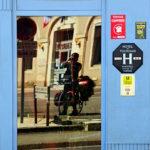 Radler mit bepacktem Reiserad hält den Fotoapparat vors Gesicht und fotografiert in eine spiegelverglaste Tür vor einem Hotel. Auf der hellblauen Fassade sind Schilder befestigt, die die Qualität des Hotels auszeichnen.