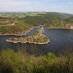 Blick vom Berg auf eine dreieckige Flussinsel. Ringsum grüne bewaldete Klippen und Hügel