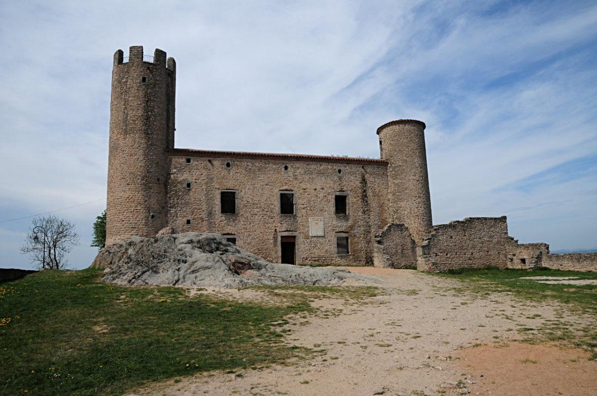 Eine karge Burgmauer mit Turm und Zinnen links und einem zinnenlosen Turm rechts.