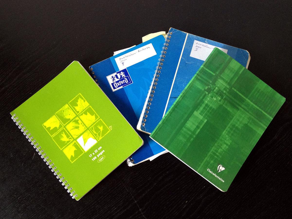 Zwei blaue und zwei grüne Notizbücher aufgefächert wie ein Kartenblatt auf schwarzem Grund