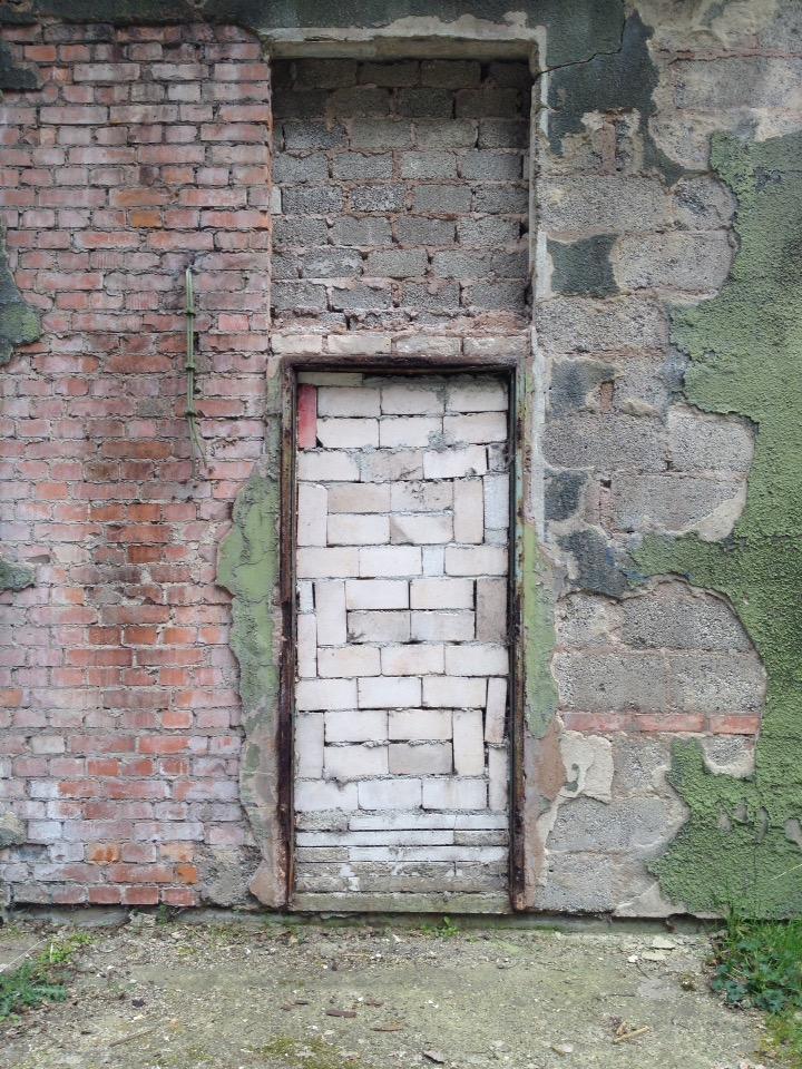 Außenwand mit abblätternder grüner Farbe. Eine Türöffnung ist mit weißen Steinen vermauert.