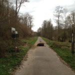 Schnurgerader Radweg in einem grünen Tal. Auf dem Weg liegt ein Felsbrocken und daneben ein Gitter, um Mehrspurige Fahrzeuge an der Durchfahrt zu hindern