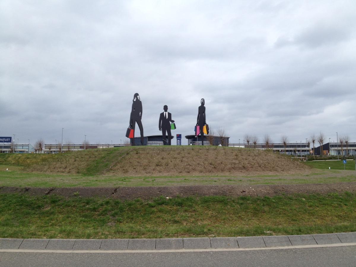 Drei shoppende Figuren, überlebensgroß auf einem Verkehrskreisel. Sie tragen Taschen.