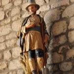 Eine bürgerliche Kaufmannsfigur aus bemaltem Holz auf einem Sockel vor der Naturstein-Kirchenwand