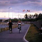 Ein Radweg kurz nach einer Straßenunterführung führt entlang eines Sees. Zwei Radlerinnen kommen entgegen. Rechts sitzt ein junger Mann in kurzen Hosen und T-Shirt in der Hocke, an die Betonmauer der Unterführung gelehnt.