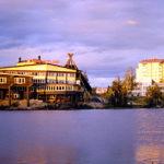 Über einen See schaut man auf zwei große Gebäude im schrägen Licht der Abendsonne