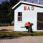 Vor einer hellblauen Umkleidehütte aus Brettern sitzt ein junger Mann, die Arme hinter dem Kopf verschränkt an der Wand lehnend, die nackten Füße hochgelegt auf einen Stuhl. An der Hütte sind die dredimensionalen Lettern BAD in roter Farbe festgeschraubt.