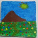 Durch eine Wiese voller Blumentupfer führt ein Weg auf einen braunen Berg zu. Im blauen Himmel scheint eine große Sonne mit roten Zacken.