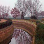 Ein tief eingeschnittener schmaler Kanal mit beidseitigen unbefestigten Wegen biegt sich in einer lInkskurve. Unbelaubte Bäume spiegeln sich im Wasser.