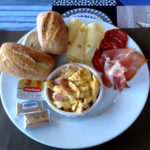 Ein FRühstücksteller mit Brötchen, Wurst, abgepackter Butter und Kartoffelsalat.