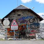 Ein Berghaus aus Natursteinen mit Krüppelwalmdach, frontal gesehen ist über und über mit Graffiti bemalt