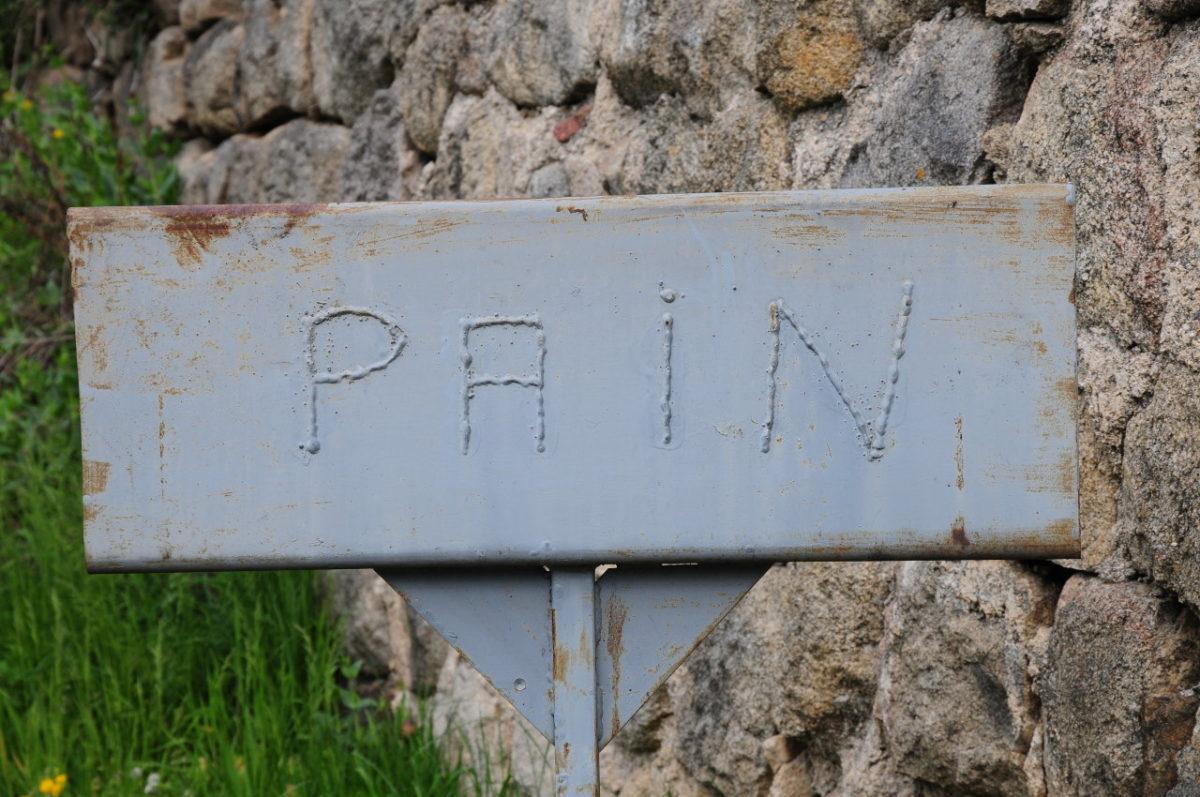 Aufgrauem Blech ist das Wort PAIN mit Schweißpunkten geschrieben