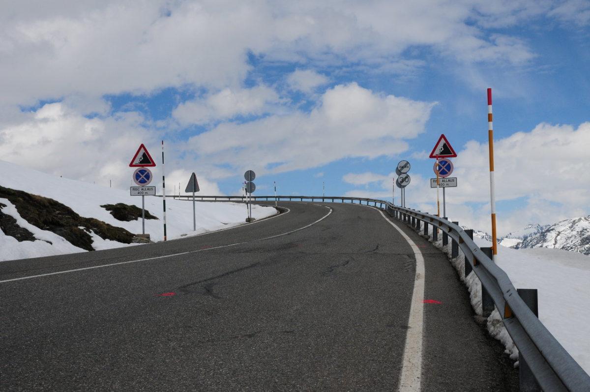 Leere, breite, von Schnee geräumte Passstraße scheint bei einer Linkskurve hinter Warnschildern beiderseits und einer Leitplanke in den hellblau bewölkten Himmel zu führen.
