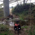 Reiserad vor einem kleinen Bach auf steiniger Piste unter zwei Straßenbrücken
