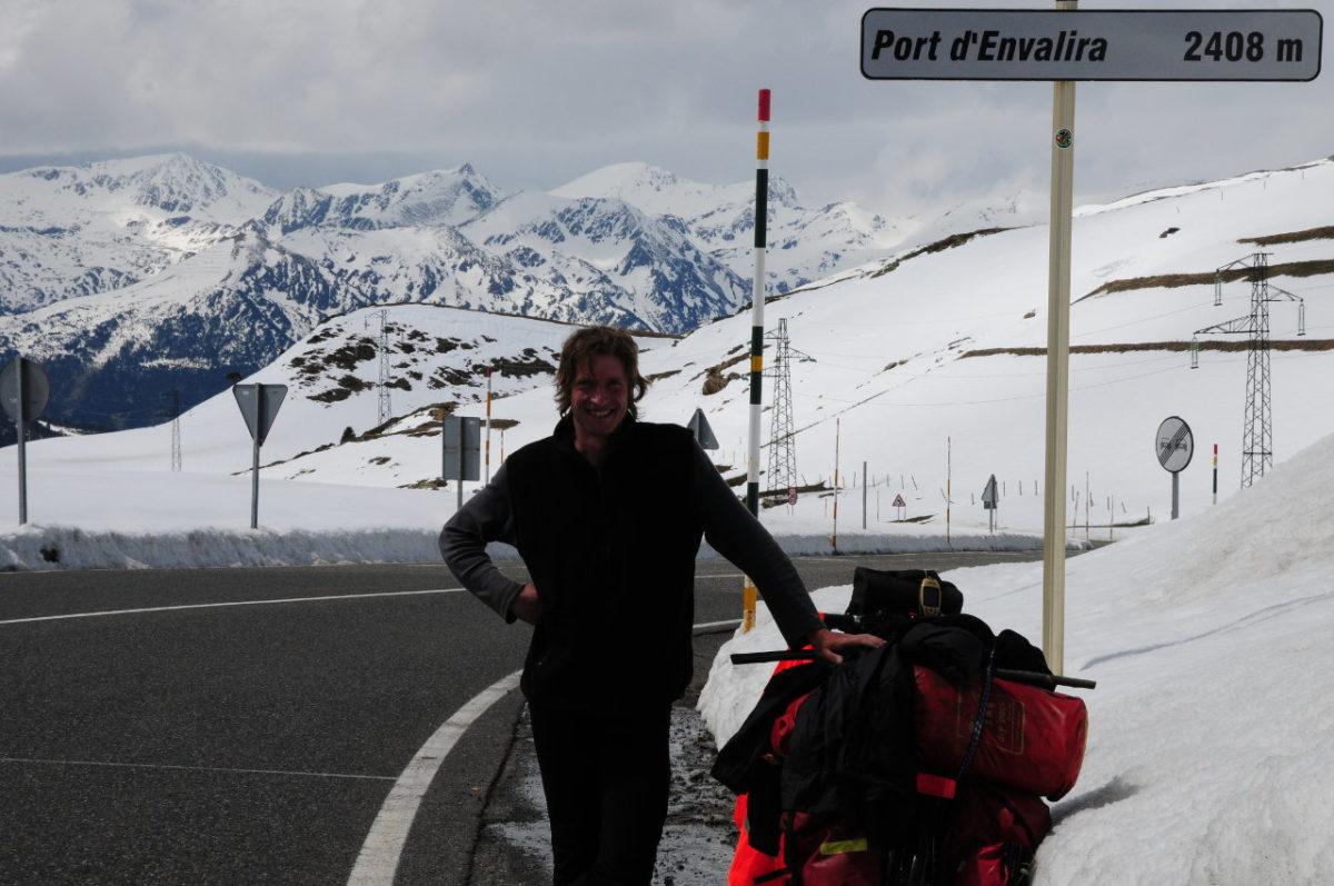 Mann stützt sich au ein Reiserad neben einem Passhöhenschild Porte d'Envalira 2408. Ringsum liegt hoher schnee. Die Straße ist geräumt
