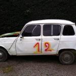 Ein weißer alter R4 im Profil. Auf seine Türen ist die Zahl 12 gesprayt. Die verbeulte Motorhaube ist auch besprayt und ragt ein bisschen nach oben.