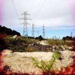 Strommasten und wie Spinnweben über den Himmel ziehende Leitungen auf karger, spanischer Landschaft. Das Bild hat eine rötliche Vignettierung zum Rand hin.