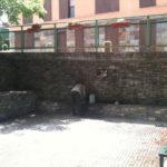 Ein Mann bückt sich vor einer langen Mauer, aus der ein Brunnen entspringt.