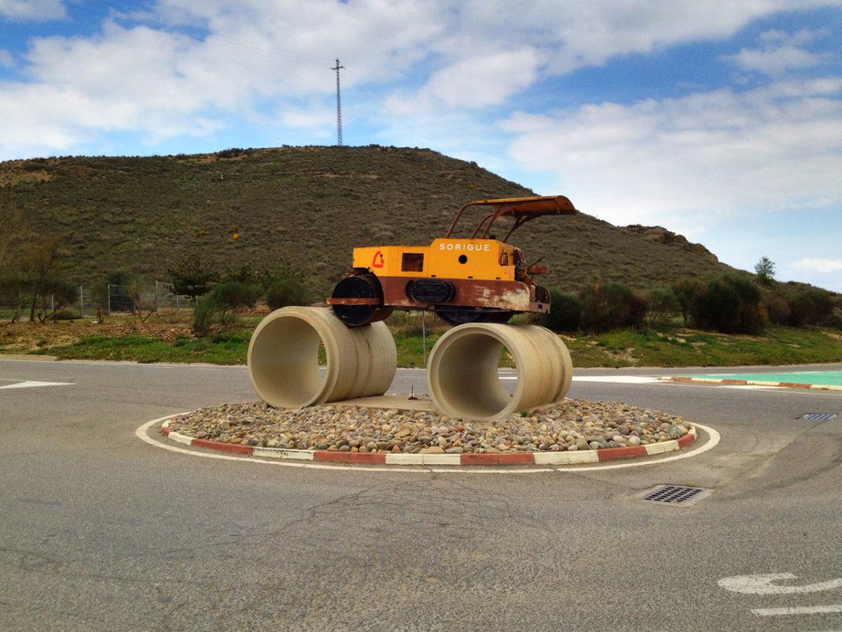 Auf einem Verkehrskreisel steht eine gelbe Walze auf zwei Betonröhren, die aussehen, als seien sie die Räder der Maschine.