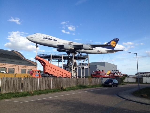 Am Verkehrsmuseum Speyer die unheimliche Boeing auf Stelzen, die fast so hoch wie der Dom über der Stadt thront, vorne Straße und Zaun, darüber Blauhimmel