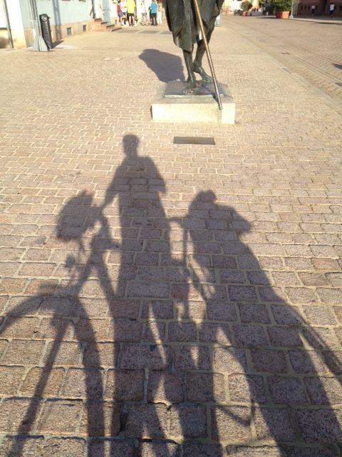 Schattenwurf des Künstlers samt Fahrrad auf rotem Klinkersteinboden. Im Hintergrund der Unterteil einer Skulptur und noch weiter hinten Menschen auf der Straße.