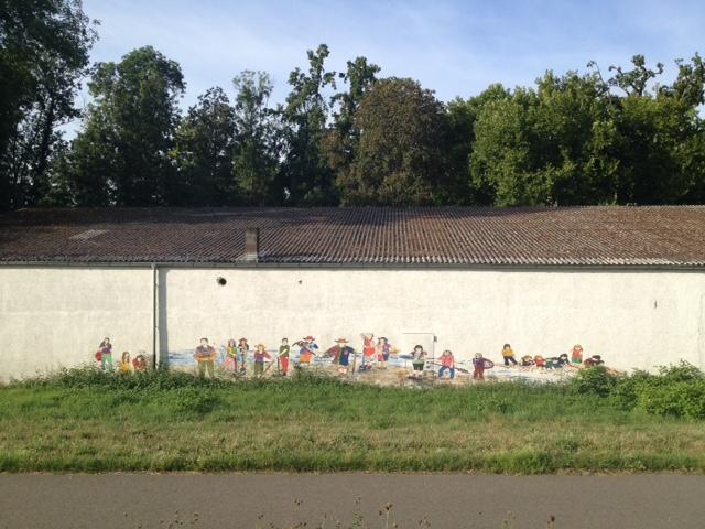 Lange Hauswand, die sich mittig quer durchs Bild zieht. Darauf gemalt sind ganz unterschiedliche Menschen bei unterschiedlichen Tätigkeiten. Darüber Dach, dahinter Bäume und Blauhimmel. Im Vordergrund Wiese und ganz vorn die Straße.