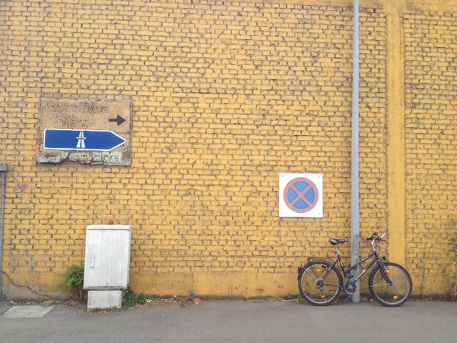 Gelbgestrichene Backsteinwand. Links im Bild Autobahwegweiser nach rechts zeigend. Rechts im Bild Absolutes Halteverbot neben einer Straßenlampenstange, an der ein Fahrrad lehnt. Vorne Straße.