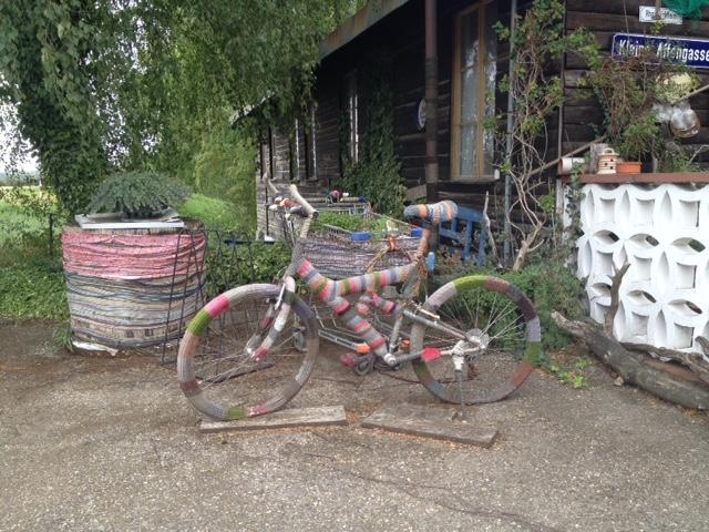 In der Bildmitte ein mit Wolle kringelig bunt eingestricktes Fahrrad als Kunstobjekt. Auf dem Platz vor einem Holzhaus stehen weitere Kunstobjekte. Dahinter ein ausladender Baum.