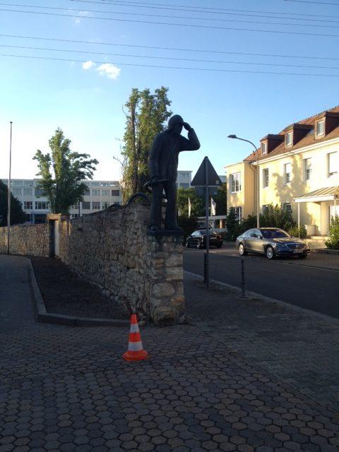 Am Ende einer Mauer aus Natursteinen, die von hinten nach vorn das Bild halbiert, steht eine menschliche Skulptur aus Metall. Die Figur hält sich, wie zum Gruß oder Fernblick, die linke Hand an die Stirn. Rechts im Bild Straße und Häuserfront, darüber Blauhimmel, links Steinboden.