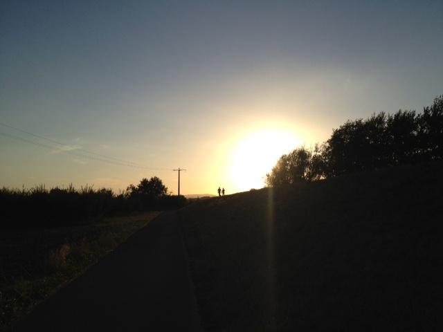 Im Gegenlicht sind in der Bildmitte zwei Menschen auf einer Anhhöe zu sehen. Die obere Bildhälfte zeigt den lilablauen Himmel bei untergehender Sonne, die untere Bildhälfte eine Art Deichmauer für die Straße, auf welcher die Menschen stehen, rechts und links davon hüglige Wiese mit Bäumen bewachsen.