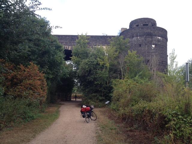 Mittig von vorn nach hinten laufender Radweg, im Hintergrund Schlossmauern, rechts und links Gebüsch.