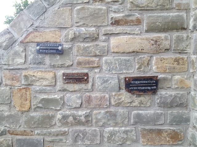Mauer aus Natursteinen mit drei unterschiedlich hoch hängenden Hochwassermarken aus unterschiedlichen Jahren, die neueste und höchste scheint die vom März 1988 zu sein.