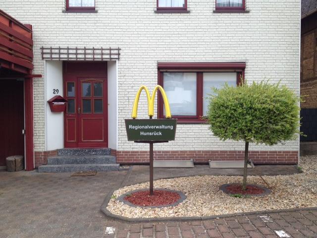 Hofplatz mit Steingarten, in welchem ein rundgeschnittenes Bäumchen steht, daneben auf einer Stange unter einem Macdonalds-Logo die Aufschrift Regionalverwaltung Hunsrück. Dahinter ein helles Backsteingebäude mit roten Zierelementen und roter Eingangstür.