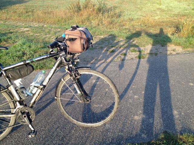 Links im Bild das Rad auf Radweg stehend, rechts im Bild der Künstler und das Rad als Schatten, im Hintergrund Wiese im und Wanderweg.