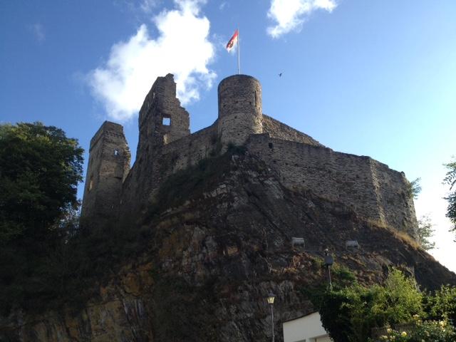 Blick von unten zu den Mauern der Burg Kastellaun hoch. Im Eckturm eine Deutschlandfahne. Am Schlossberg Hecke, Gebüsche, Bäume. Darüber Blauhimmel mit einzelnen Wolken.