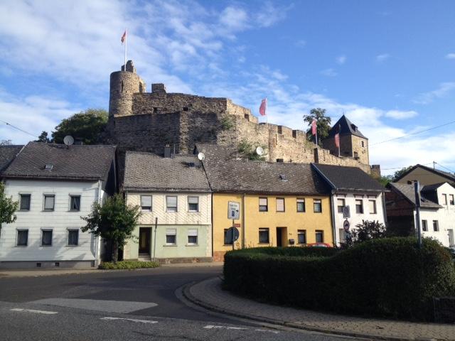 Kastellaun, nochmals im Hintergrund die Burg, vorne eine Häuserzeile, die Straße, die eine Kurve macht, rechts Hecken. Über allem wolkiger Blauhimmel.