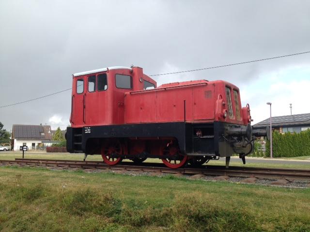 Rote Lokomotive auf dem Abstellgleis, vorne Wiese, hinten Häuser und Grauhimmel.
