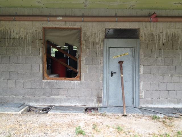 Baustelle. Neubaufassade mit Fensteröffnung, die behelfsmäßig mit Stoff verschlossen ist. Der Stoff ist halb zerrissen. Rechts daneben eine Metalltür, die mit einer schweren Metallstange zugesperrt ist. Darüber ein dickes Kupferrohr quer durchs Bild.