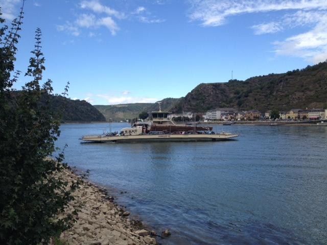 Ein Fährschiff quert den Rhein. Vorne Sandstrand und Gebüsch, hinten das andere Ufer, ein Ort, Hügel, darüber Blauhimmel