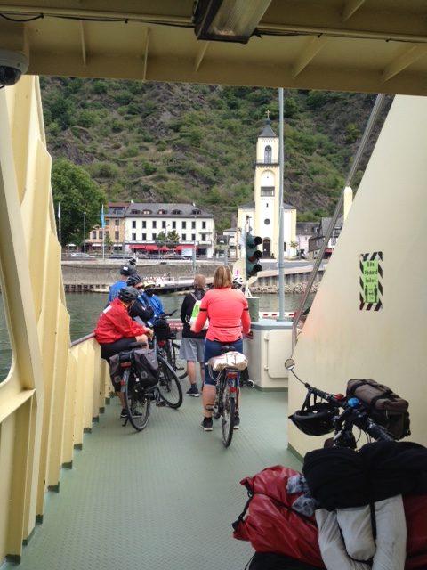 Auf der Fähre. Ein Ausblick auf andere Radler:innen auf der Fähre, vorne bereits das andere Ufer mit einem hohen Kirchturm. Im Vordergrund rechts noch das Künstlerrad, schwer beladen.