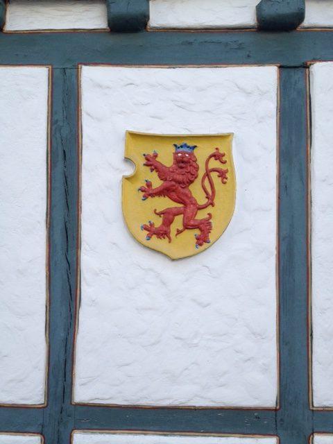 Wappentier auf weißer Fassade von blauem Fachwerk eingerahmt. Das rote Wappentier ist ein zweischwänziger Drachen mit blauer Krone auf gelbem Wappenhintergrund.