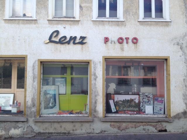 Schaufenster eines ehemaligen Photobedarf-Geschäftes. Der Schriftzug Lenz und Photo ist noch zu lesen, das H von Photo fehlt. Die Fenster sind mit Bildern dekoriert. Die Fassade ist verblichen. Die Fenster im ersten Stock sehen verwahrlost aus.