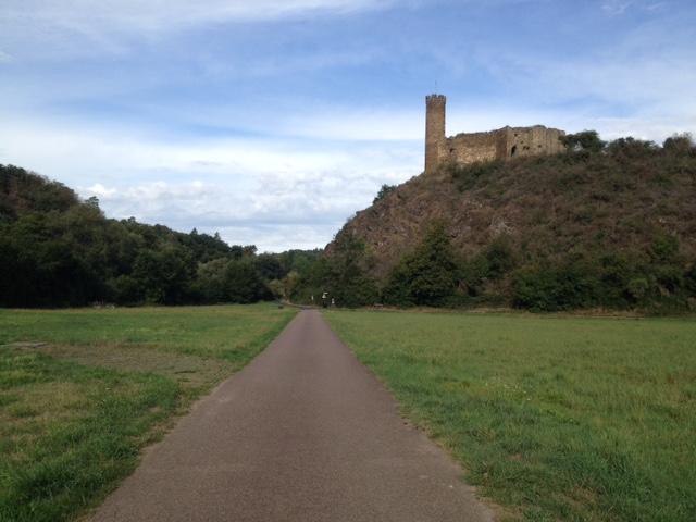 Mittig von vorn nach hinten verlaufender Radweg, rechts und links Wiesen, im rechten Hintergrund ein Hügel mit einer Burg samt Hügel. Links Wald, darüber wolkiger Blauhimmel.