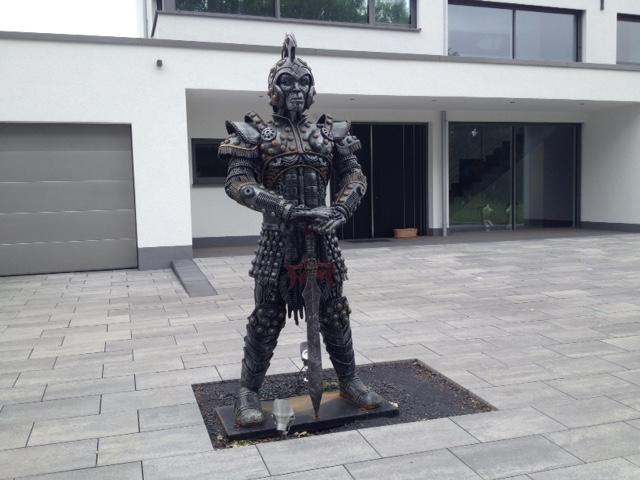 Ritterrüstungskulptur aus Metall in Habachtstellung auf Metallplatte auf grauem Plattenboden vor modernem Gebäude.